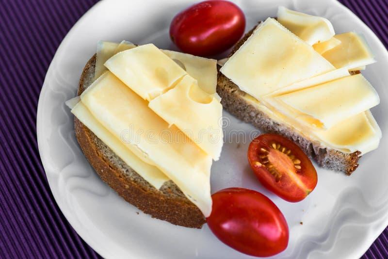 Emmental ser na dwa chlebach z pomidorem na bielu talerzu zdjęcie royalty free