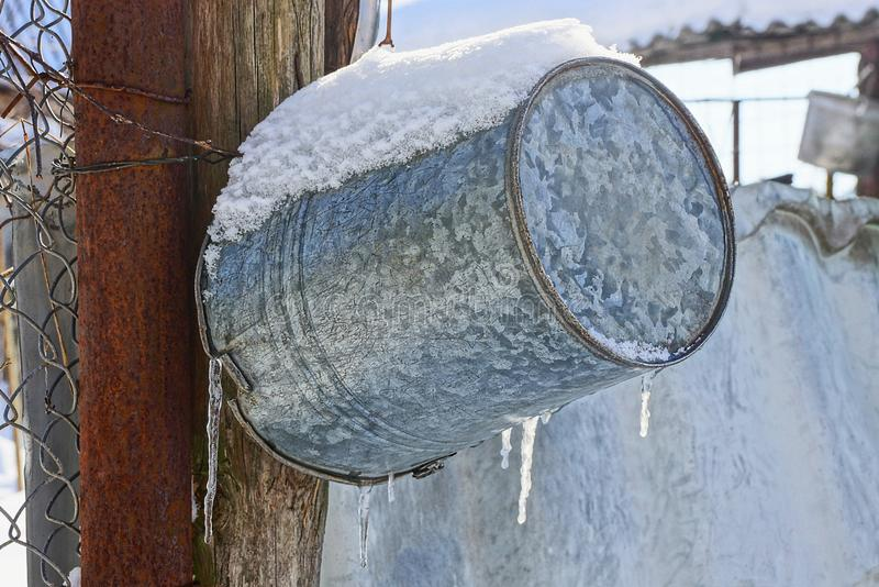 Emmer het hangen op de straat onder sneeuw en ijskegels stock foto