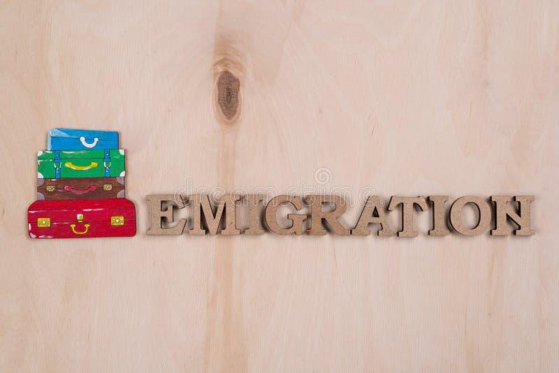 Emmigration ordet i abstrakta träbokstäver Bakgrundsträyttersida och en hög av resväskor royaltyfria bilder