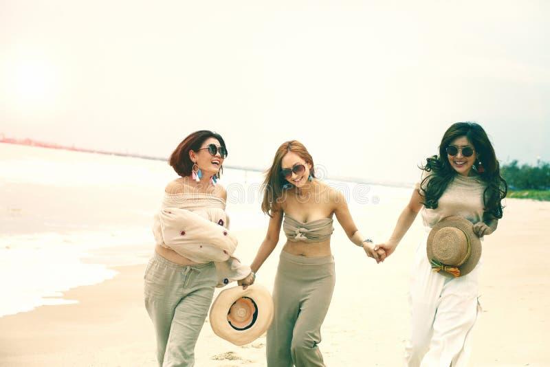 Emoção asiática alegre da felicidade da mulher três na praia do mar das férias fotos de stock royalty free