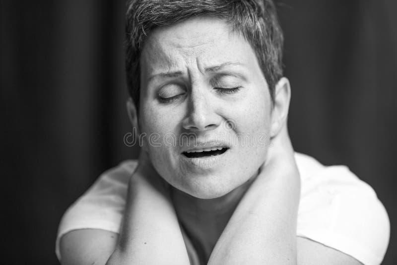 Emoção de sofrimento na cara de uma mulher adulta com um cabelo cinzento curto Retrato preto e branco Close-up imagens de stock royalty free