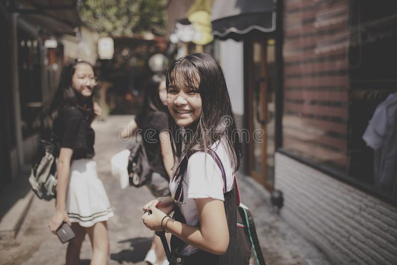 Emoção de sorriso da felicidade da cara do adolescente asiático que anda na rua do citylife fotos de stock