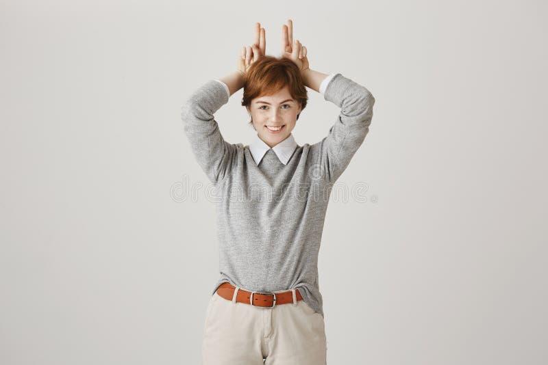 Emoções e conceito positivos da linguagem corporal Ruivo encantador com as sardas e o sorriso adorável que mostram o sinal de v a imagem de stock