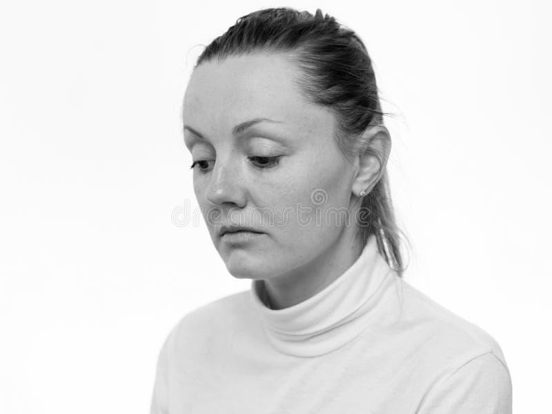 emoções Feche acima do retrato de uma mulher triste que olha isolada para baixo no fundo branco imagem de stock