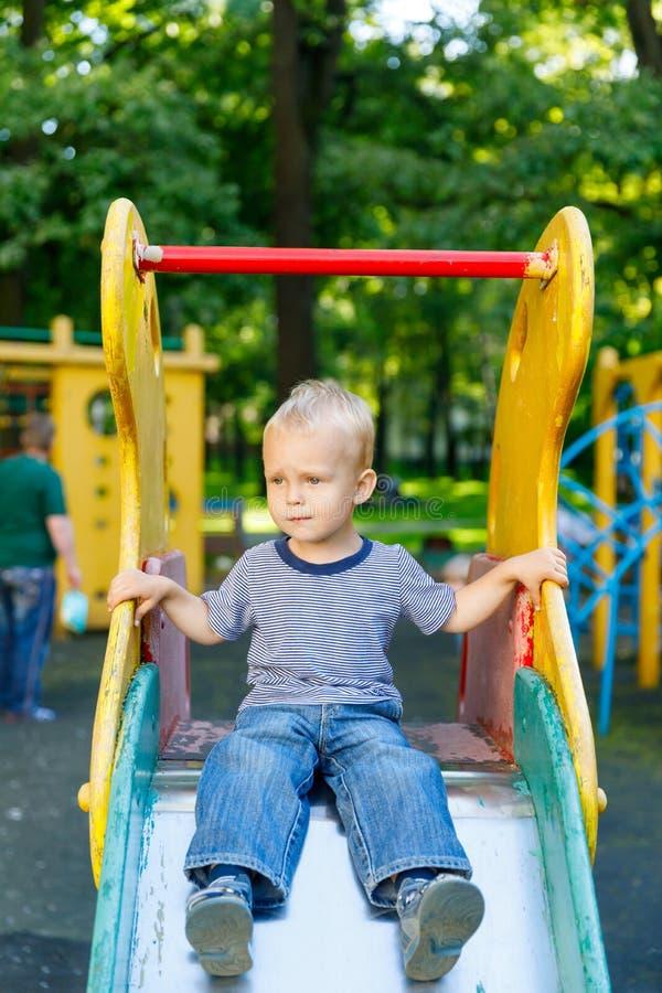 Emoções na opinião, na confusão e na tristeza do ` s da criança nos olhos do rapaz pequeno que senta-se no monte do ` s das crian fotos de stock