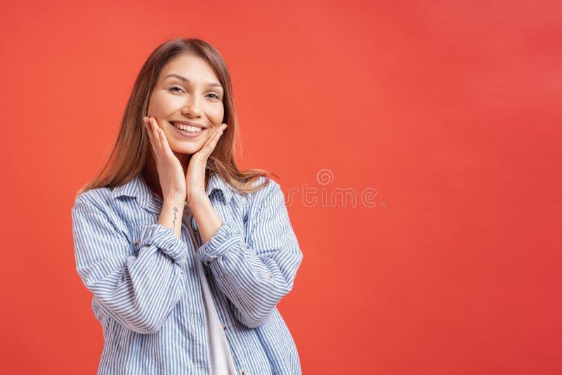 Emo??es dos povos - retrato da menina positiva surpreendida sobre o fundo vermelho fotos de stock