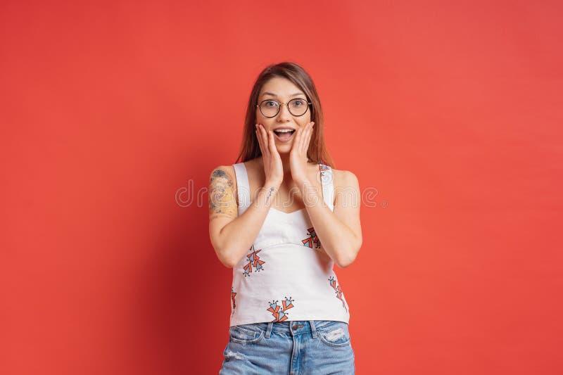 Emo??es dos povos - retrato da menina positiva surpreendida sobre o fundo vermelho foto de stock