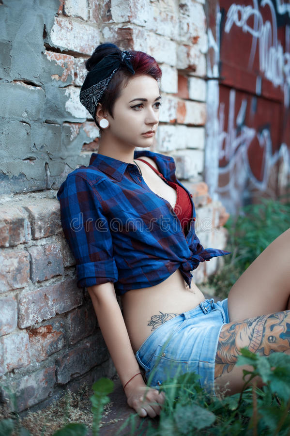 Emo girl in pin-up sits near a brick wall royalty free stock images