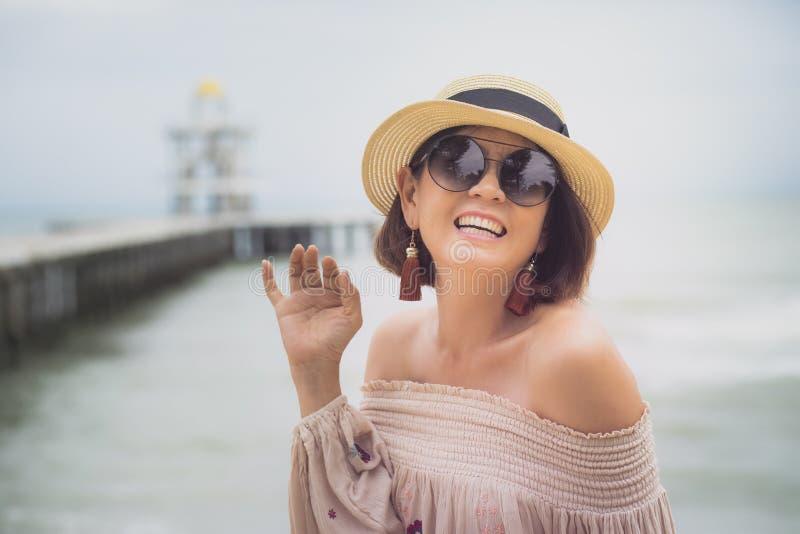 Emoción asiática alegre de la felicidad de la mujer en la playa del mar fotos de archivo