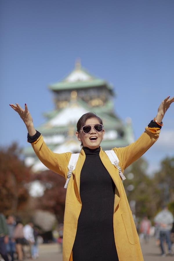 Emoción asiática de la felicidad de la mujer que viaja delante del castillo de Osaka imagen de archivo libre de regalías
