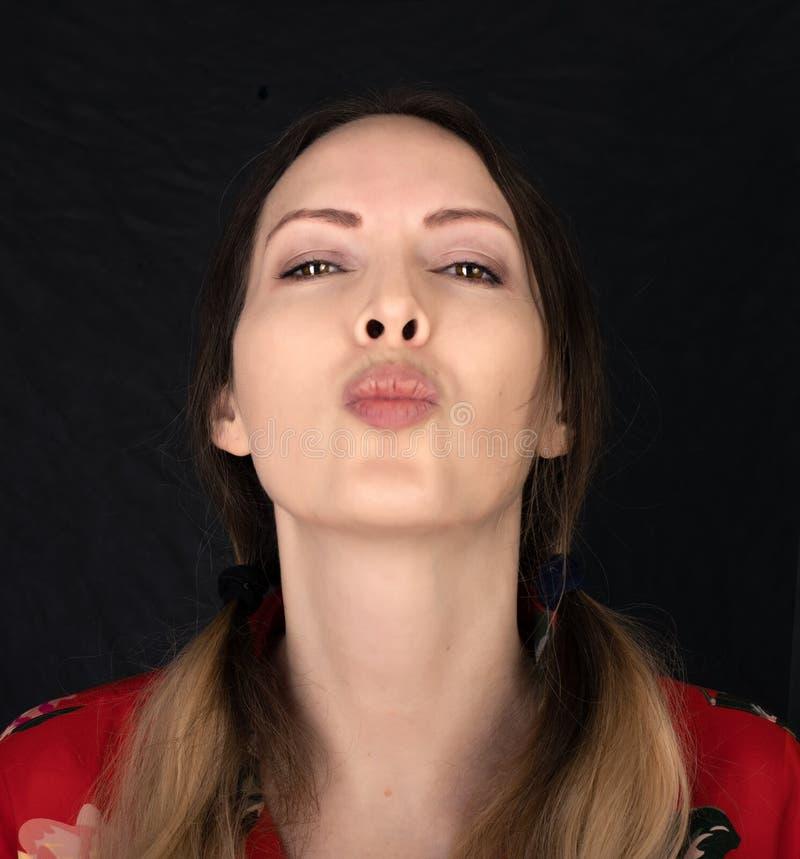 Emoción Cara de mujer cerrada con expresiones faciales sobre fondo negro fotos de archivo