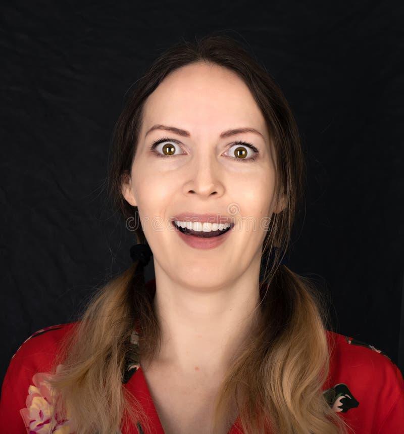Emoción Cara de mujer cerrada con expresiones faciales sobre fondo negro imagenes de archivo