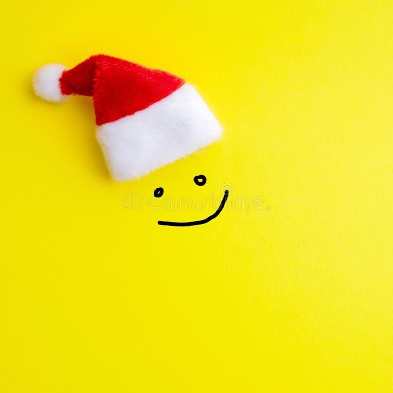 Emoción de expresiones faciales sonrientes alegres y un sombrero rojo de Santa Claus en un fondo amarillo Concepto de Feliz Año N foto de archivo libre de regalías