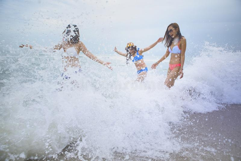 Emoción de la felicidad de tres mujeres con salpicar la onda de la playa del mar fotos de archivo