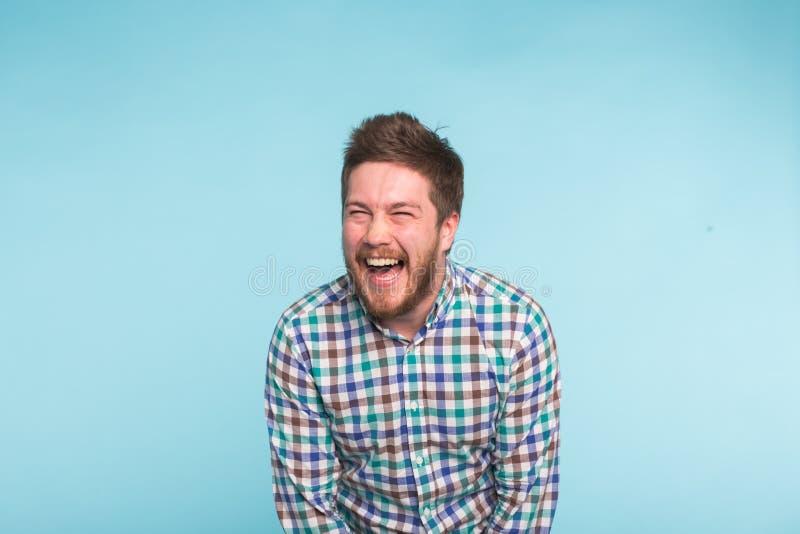 Emoción, gente y concepto de la diversión - hombre hermoso joven que ríe en fondo azul imagen de archivo libre de regalías