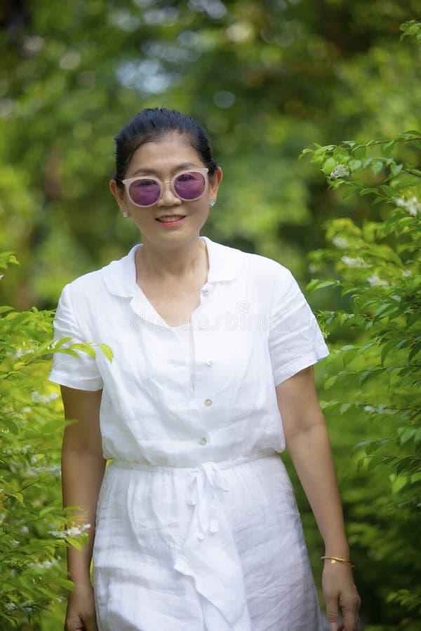 Emoción sonriente dentuda de la felicidad de la cara de la ropa blanca de la mujer que lleva en jardín verde de las hojas imagenes de archivo