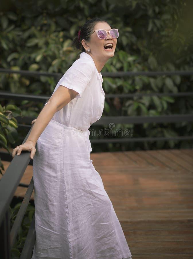 Emoci?n sonriente dentuda de la felicidad de la cara de la ropa blanca de la mujer que lleva en jard?n verde de las hojas imagenes de archivo