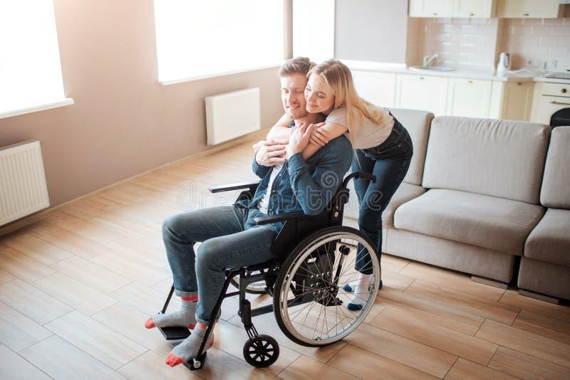 Emociones alegres Hombre joven con la incapacidad que se sienta en la silla de ruedas Soporte de la mujer detr?s y abrazarlo Pare imágenes de archivo libres de regalías