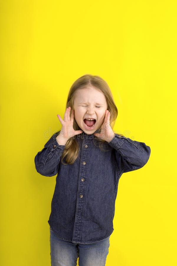 Emociones de griterío de la niña en fondo amarillo imágenes de archivo libres de regalías