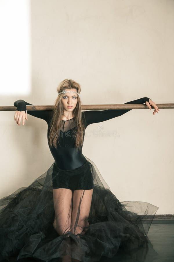 Emociones de un bailarín de ballet en la barra del ballet en sus rodillas foto de archivo