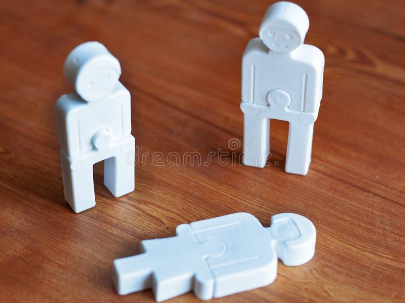 Emociones del pesar entre la gente, el concepto de la ayuda social, pequeños hombres del juguete en un fondo de madera imagenes de archivo