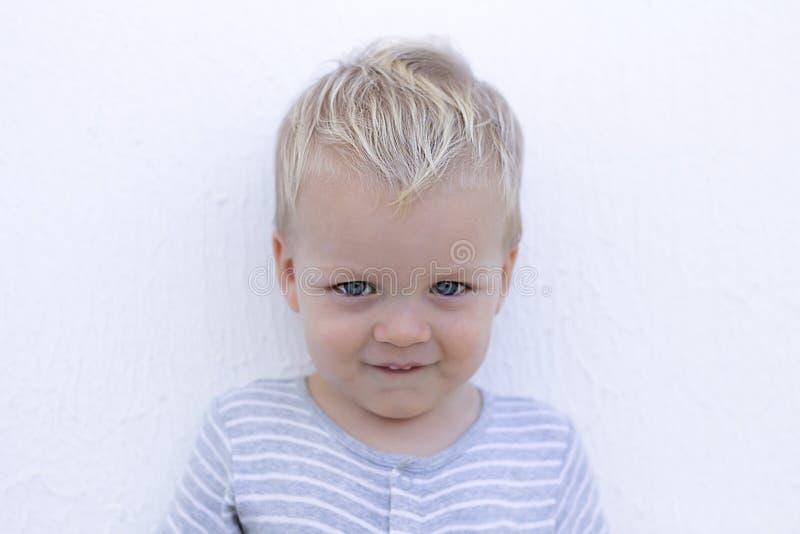 emociones Niño tímido contra la pared Retrato del primer del niño pequeño lindo imágenes de archivo libres de regalías