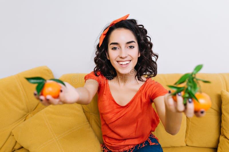 Emociones positivas verdaderas brightful del retrato de la mujer joven alegre emocionada que sonríe a la cámara con las mandarina fotos de archivo