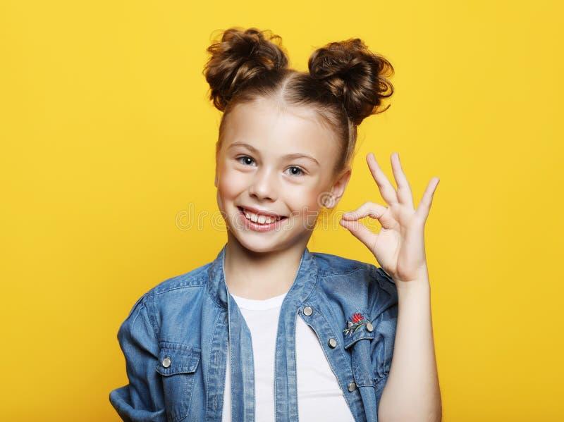 Emocja, dzieciństwo i ludzie pojęć: mała dziewczynka pokazuje ok gest obrazy stock