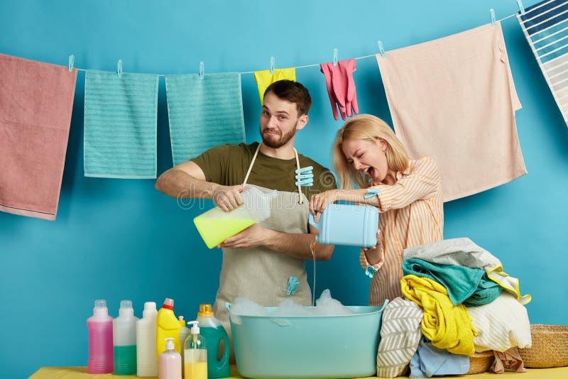 Emocjonalna blondynki kobieta i beraded mężczyzna z detergentami w ich rękach zdjęcie stock