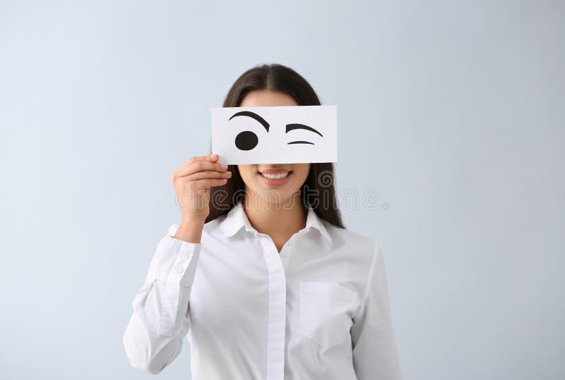 Emocjonalna młoda kobieta chuje twarz za prześcieradłem papier z patroszonymi oczami na lekkim tle obrazy royalty free