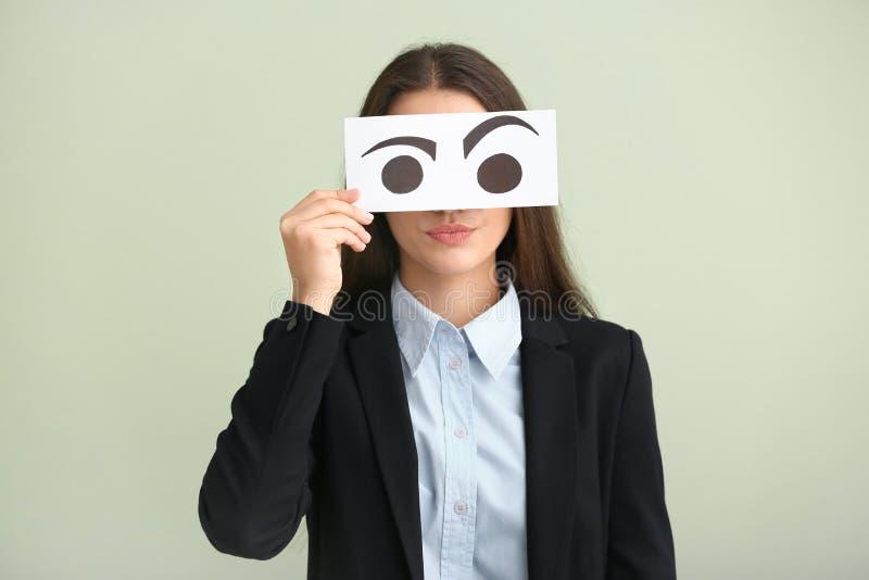 Emocjonalna młoda kobieta chuje twarz za prześcieradłem papier z patroszonymi oczami na lekkim tle obrazy stock