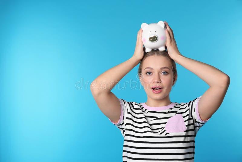 Emocjonalna młoda kobieta z prosiątkiem i przestrzeń dla teksta na koloru tle pieniądze oszczędzanie zdjęcie stock