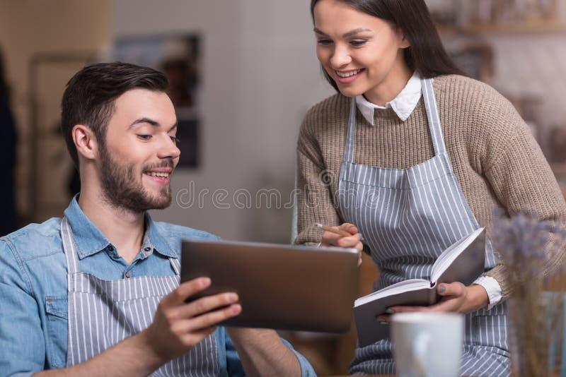 Emocjonalna potomstwo para robi notatkom i używa pastylkę zdjęcie stock