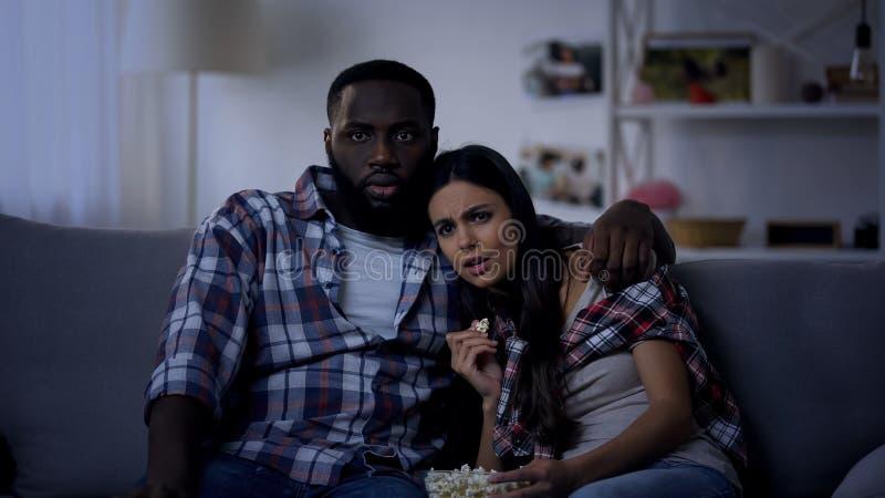 Emocjonalna rasy para z wystrzał kukurudzy dopatrywania horrorem, wieczór w domu zdjęcia royalty free