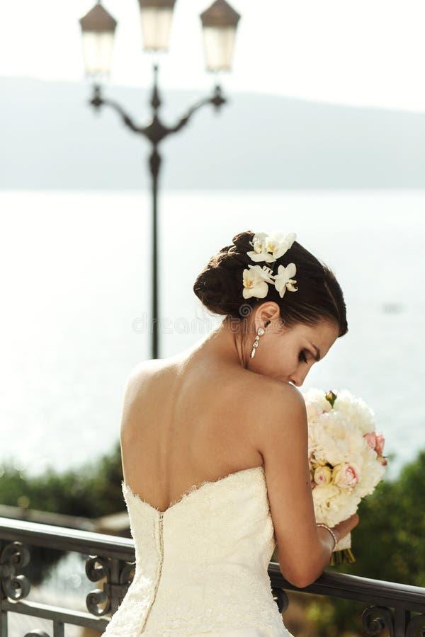 Emocjonalna seksowna brunetki panna młoda w bielu smokingowy pozować przy balkonem n obrazy stock