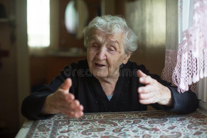 Emocjonalna starsza kobieta mówi, że gestykuluje siedząc przy stole obraz royalty free