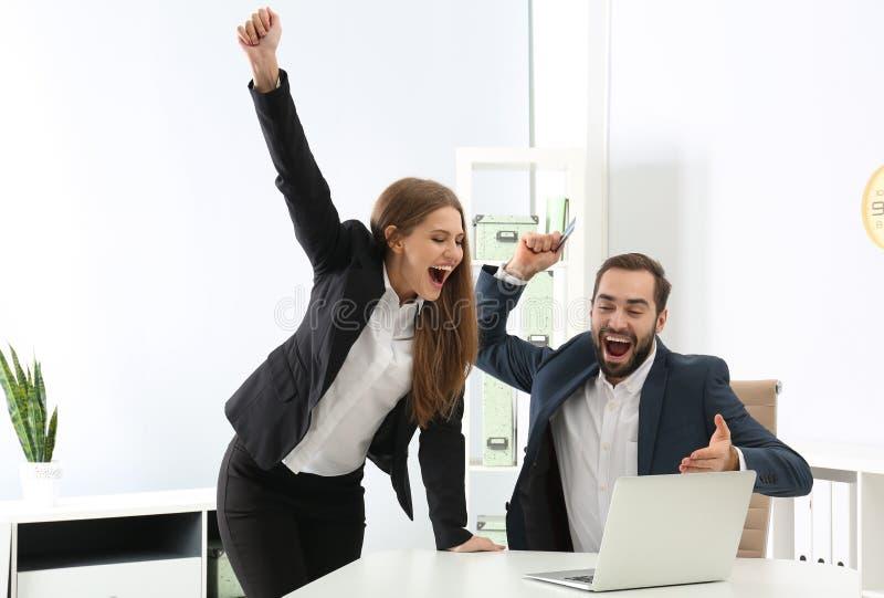 Emocjonalni młodzi ludzie z karty kredytowej i laptopu odświętności zwycięstwem obrazy royalty free