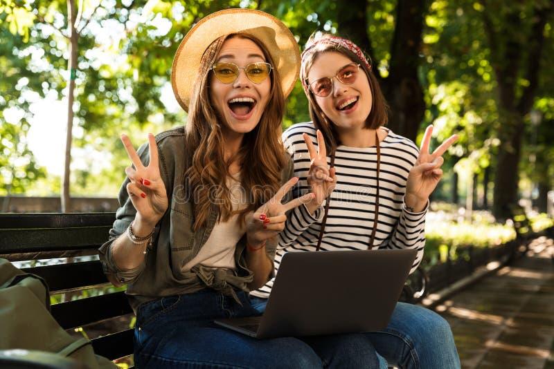Emocjonalni z podnieceniem szczęśliwi dama przyjaciele outdoors siedzi używać laptop pokazuje pokoju gest zdjęcia stock