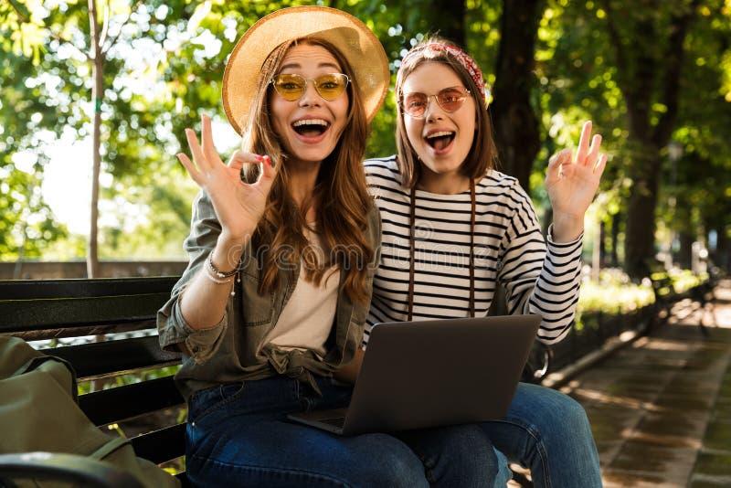 Emocjonalni z podnieceniem szczęśliwi dama przyjaciele outdoors siedzi używać laptopu seansu ok gest zdjęcia stock
