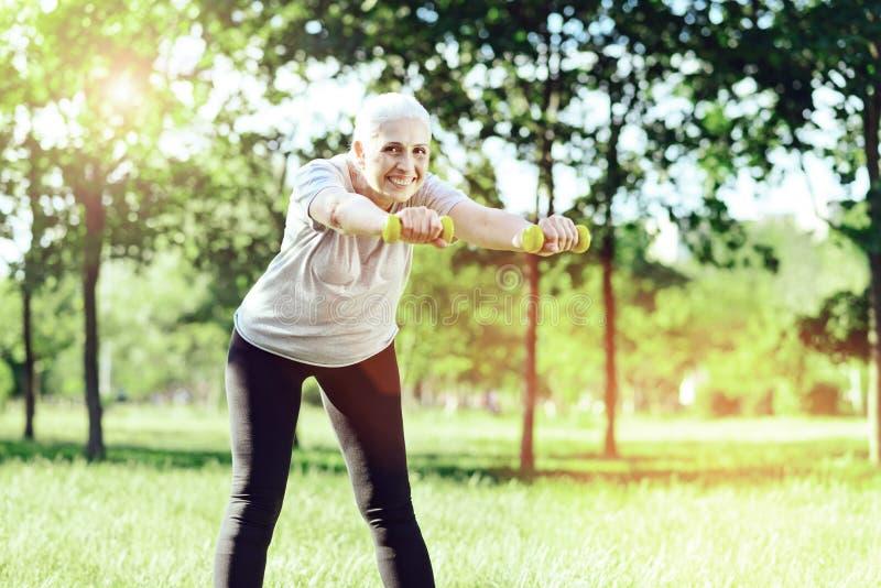 Emocjonalny aktywny emeryt patrzeje szczęśliwy podczas gdy trenujący fotografia royalty free