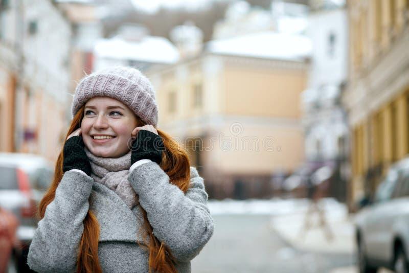 Emocjonalny czerwony z włosami wzorcowy jest ubranym ciepłej zimy odzieżowy chodzący d obrazy stock