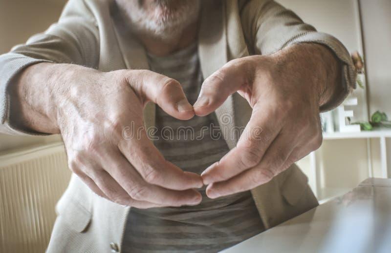 Emocjonalny dojrzały biznesmen kuje ręki serce zdjęcia stock