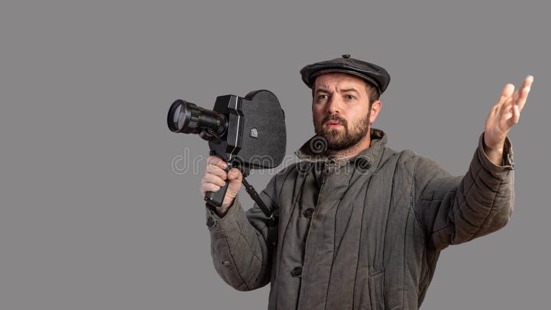 Emocjonalny kamerzysta z retro kamerą w jego rękach, studio strzał Staromodny odzież styl Komiczny spojrzenie Pojęcie - film zdjęcie stock