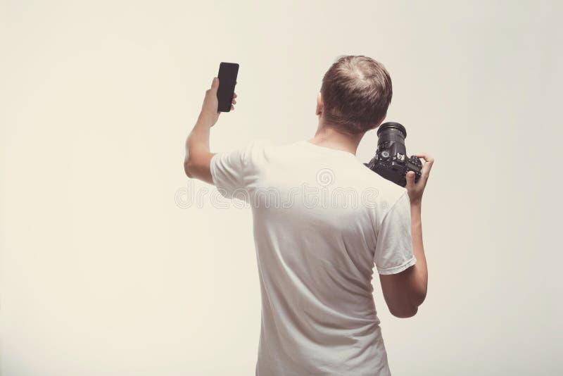 Emocjonalny mężczyzna z kamerą odizolowywającą na lekkim tle Młodego człowieka chwyta cyfrowa kamera i smartphone Styl życia, pod zdjęcie stock