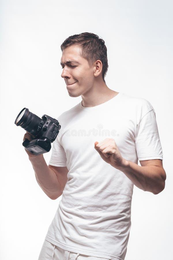 Emocjonalny mężczyzna z kamerą odizolowywającą na lekkim tle Młodego człowieka mienia kamera z zwycięstwo tanem Styl życia, podró obraz royalty free