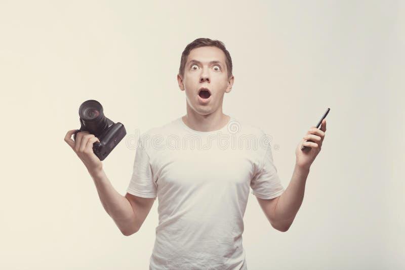 Emocjonalny mężczyzna z kamerą odizolowywającą na lekkim tle Młodego człowieka mienia smartphone i kamera Styl życia, podróż i te obrazy stock