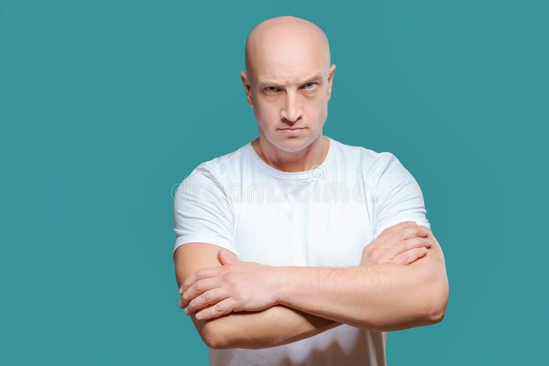 Emocjonalny mężczyzna w białej koszulce z gniewnym wyrazem twarzy na tle, odosobnienie obrazy royalty free