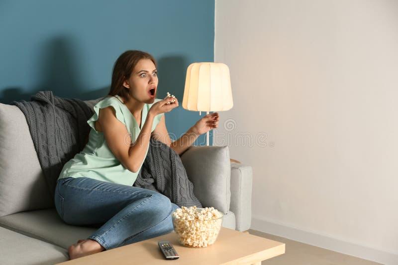 Emocjonalny młodej kobiety łasowania popkorn podczas gdy oglądający TV w domu zdjęcie royalty free