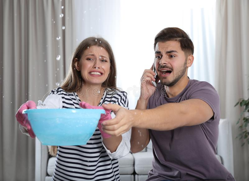 Emocjonalny młodej kobiety kolekcjonowania wody wyciek od sufitu podczas gdy jej mąż dzwoni hydraulika obraz stock