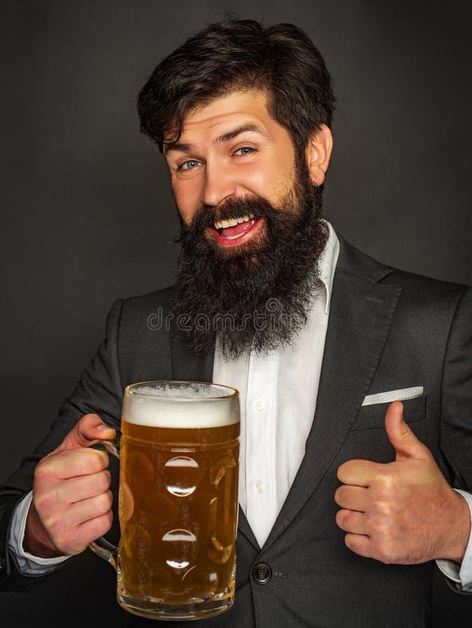 Emocjonalny ?mieszny brodaty pij?cy modnisi?w chwyt?w rzemios?o butelkowa? piwo Broda m??czyzna pije piwo od piwnego kubka zdjęcia stock